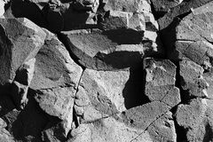Weathered basaltic rock face - cracks and shadows. Weathered and cracked basaltic rock face with interesting fissures, crack patterns and shadows stock image