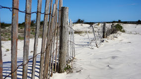 Weathered beach fence along sand dunes Stock Photos