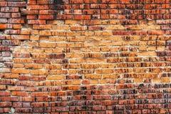 Weathered befleckte alte orange Backsteinmauer, Beschaffenheitsschmutzhintergrund Lizenzfreie Stockfotografie