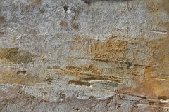 Weathered beige facade. Grunge light orange brown concrete plaster facade of old house as weathered abstract background royalty free stock photography