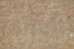 Weathered beige facade. Grunge light orange brown concrete plaster facade of old house as weathered abstract background royalty free stock image