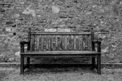A weathered bench in front of a castle wall royalty free stock images
