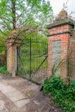 Weathered black painted iron gate between brick pillars Royalty Free Stock Photo