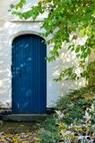 Weathered blue door and white wall Royalty Free Stock Image