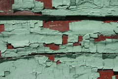 Weathered board (green/red). Closeup of a run-down building, paint chips showing two colors Stock Photos