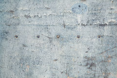 Weathered board with old blue paint and bolts Stock Images