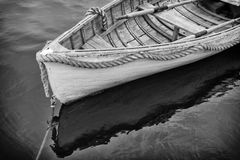 Weathered. A weathered boat with the reflections and strong heavy rope around its bow royalty free stock images