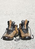 Weathered boots. Weathered trekking boots on gravel Stock Photos
