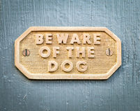 Weathered Brass Sign BEWARE OF THE DOG on Grey Gate Photo libre de droits