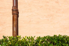 Weathered brick wall with pipe gutter. Detail of the facade of a house. Photograph taken outdoors Background of brick. Wall and pipe stock photography