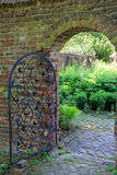 Weathered brick walls and gate leading into Summer garden Royalty Free Stock Image