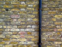 Weathered bricks wall and black tube of London. Old brick wall patinated and colored. Rough texture. Black metal tube. Details of the facade of a house in London stock photo