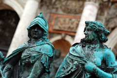 Weathered bronze statues. A closeup view of two old weathered statues of medieval figures Stock Image