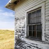 Weathered building. Exterior of weathered abandoned building with peeling paint and window in grassland Stock Photo