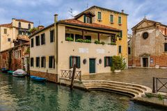 Weathered building facade on a picturesque canal in Venice Italy. Venice, Italy - September 23, 2017: Typical view of a weathered building facade on a royalty free stock photos