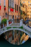 Weathered building facade on a picturesque canal in Venice Italy. Typical view of a weathered building facade and bridge on a picturesque canal in Venice, Italy royalty free stock photo
