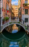Weathered building facade on a picturesque canal in Venice Italy. Typical view of a weathered building facades and bridge on a picturesque canal with reflections stock image
