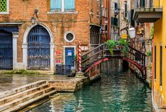 Weathered building facade on a picturesque canal in Venice Italy. Venice, Italy - September 24, 2017: Typical view of a weathered building facade and bridge on a royalty free stock photography