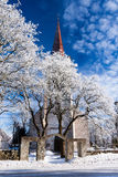 Weathered catholic church on a snowy trees Stock Image