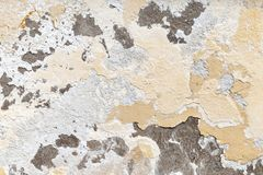 Weathered concrete old wall. Weathered concrete wall with damaged layers of white stucco and yellow paint, grungy background photo texture stock image