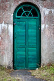 A weathered concrete outdoor underground cellar with green wooden door. A weathered concrete outdoor underground cellar with green wooden door for food storage Stock Images