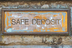 Weathered copper bank placard with the text safe deposit. On an ancient brick wall Stock Photo