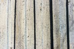 Weathered cracked blue color paint on rustic wooden crooked fence.  royalty free stock image