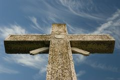 Weathered cross blue sky and wispy clouds. A worn cross reaches skyward into the wispy clouds royalty free stock image