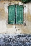 Wooden shutter on the facade of a slum. Weathered and dirty slum in a French village royalty free stock photography