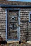 Weathered shack  door with anchor porthole Royalty Free Stock Photo