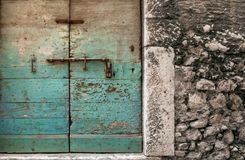 Weathered door with fading, turquoise paint. Bolted and locked, old wooden door with rough texture of peeling, turquoise paint Stock Image