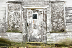 Weathered Door. An old, weathered, rustic, shack doorway with the paint peeling off and green mold Stock Image