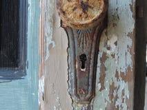 Weathered door. Rustic door knob with key Royalty Free Stock Image