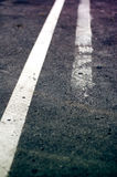 Weathered double white line on asphalt road. Right line half-effaced stock photography