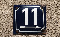 Weathered enameled plate number  11. Weathered grunge square metal enameled plate of number of street address with number 11 closeup Stock Photography