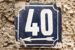 Weathered enameled plate number 40. Weathered grunge square metal enameled plate of number of street address with number 40 closeup Stock Photo