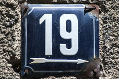 Weathered enameled plate number 19. Weathered grunge square metal enameled plate of number of street address with number 19 closeup Stock Photo