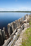 Weathered Ends. Deer Lake Newfoundland showing Perspective View of Weathered Dock Piles with Glassy Lake in Background Royalty Free Stock Images
