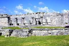 The weathered exterior wall of the ancient Mayan building ruins against blue sky in Tulum, Mexico Stock Photo