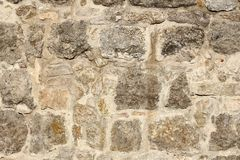 Weathered fieldstone wall with lichens in sunlight.  Royalty Free Stock Photography