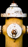 Weathered Fire Hydrant. Weathered and rusty yellow fire hydrant with black background - emergency services stock photo