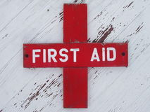 Weathered First Aid Sign. On a weathered white background Stock Photography