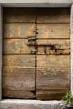 Weathered, forsaken door, boltede and locked. Bulky, old door, bolted and locked, made of rotten wooden boards covered with wormholes cracks, nails and layers of Stock Images