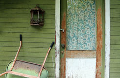 Weathered Front Door with Vintage Curtains on a Green Far Stock Image