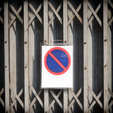 Weathered garage door with no parking sign Royalty Free Stock Photos