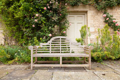 Weathered garden bench in landscaped setting Royalty Free Stock Photos