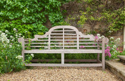 Weathered garden bench in landscaped setting Stock Photo