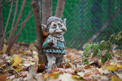 Weathered Garden Gnome. Resting against a tree Stock Images