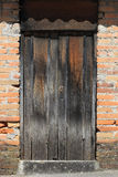 Weathered Gray Door in a Brick Wall Stock Images