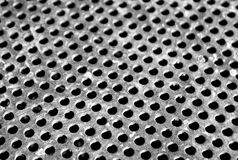 Weathered gray metal surface with holes and blur effect Stock Image